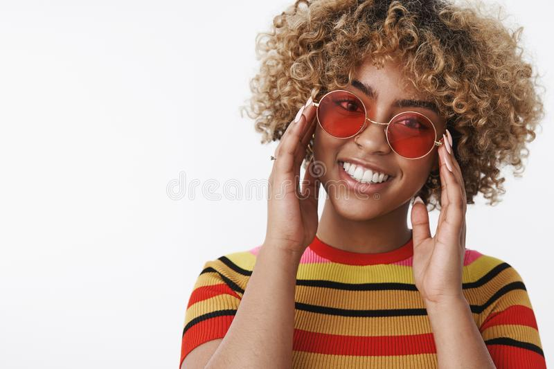 Fashion diva ready for walk. Good-looking stylish and happy african american girl with blond curly hair in trendy round. Sunglasses tilting head touching frames stock photos