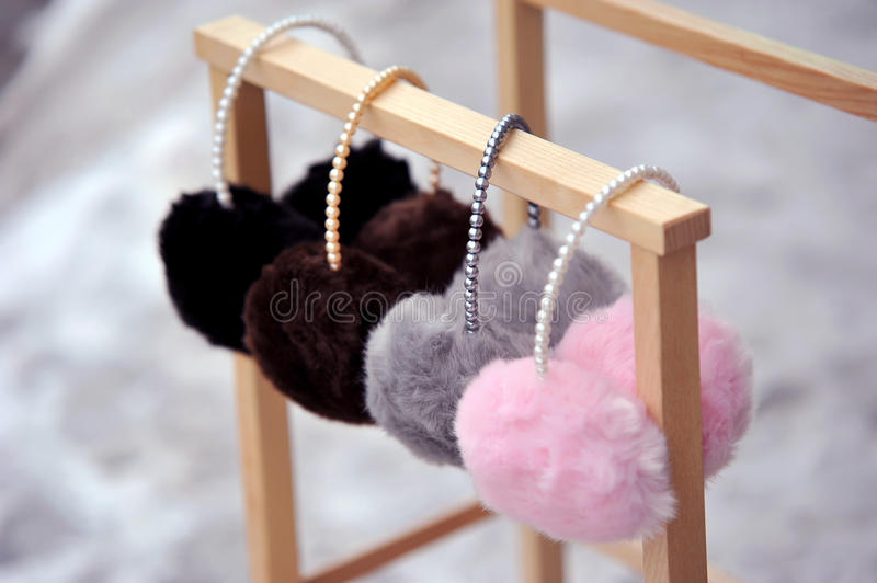 Fashion ear muffs. Pretty pink, gey and black fluffy ear mufs royalty free stock images