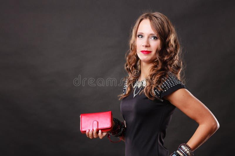 Elegant woman holding red handbag clutch bag. Fashion elegant evening outfit. Close up elegant woman holding red leather handbag clutch bag on dark background stock photography