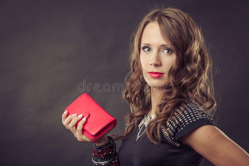 Elegant woman holding red handbag clutch bag. Fashion elegant evening outfit. Close up elegant woman holding red leather handbag clutch bag on dark background royalty free stock image