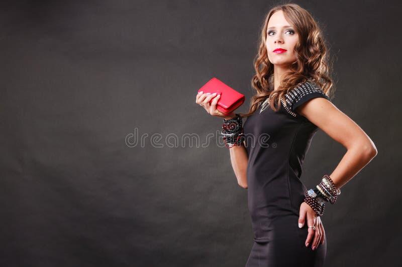 Elegant woman holding red handbag clutch bag. Fashion elegant evening outfit. Close up elegant woman holding red leather handbag clutch bag on dark background stock photos