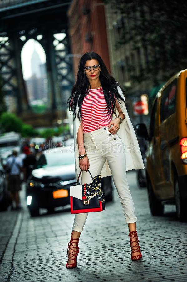 Fashion elegant stylish woman posing on the city street in summer evening weather. Sensual brunette vogue girl street style shooting royalty free stock photo