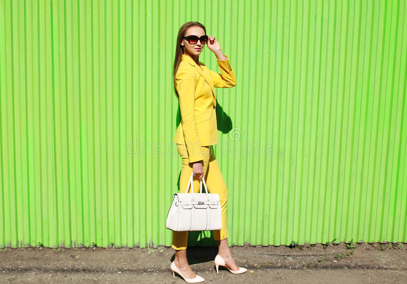 Fashion elegant young woman in yellow suit clothes with handbag stock image