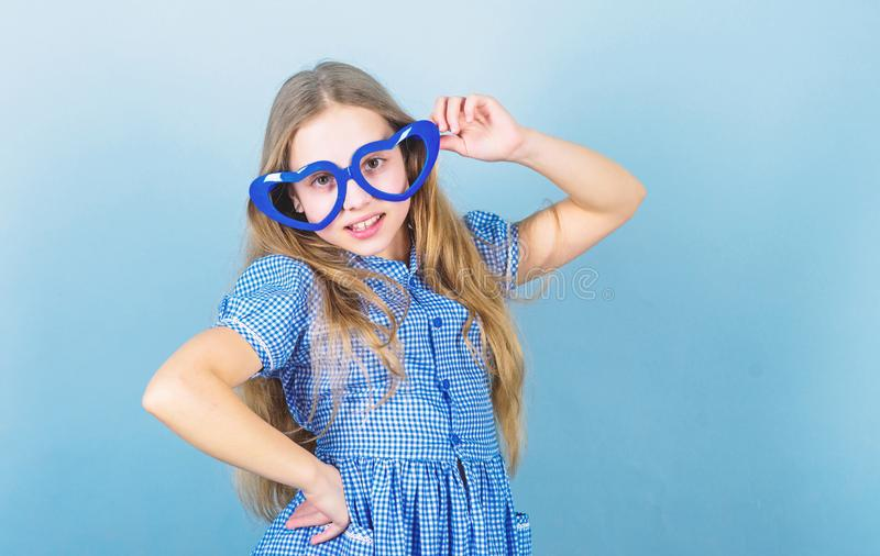 Fashion eyewear. Kid girl heart shaped eyeglasses. Girl adorable smiling face fall in love. Child charming smile blue stock images