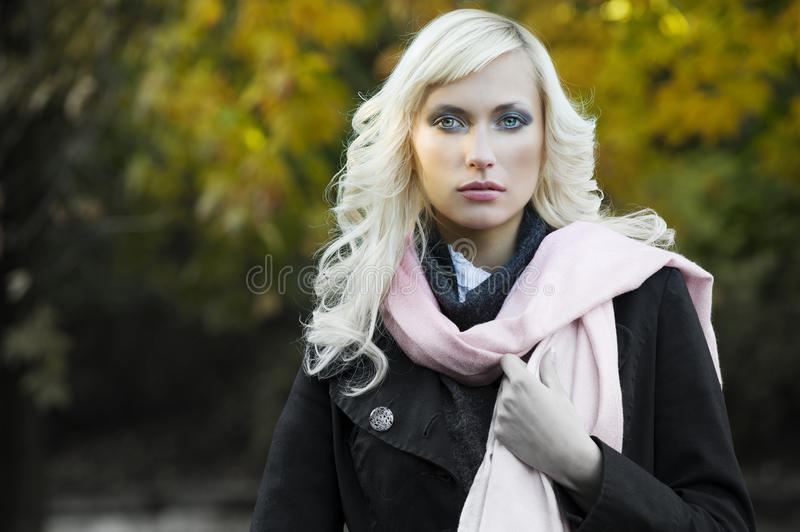 Fashion fall portrait. Close up fashion portrait of a blond girl with hair style in black coat and pink scarf with forest in background stock photo