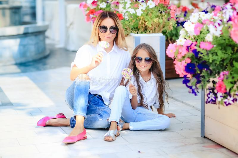 Fashion family concept - stylish mother and child wear. A portrait of a happy family: a young beautiful woman with her royalty free stock images