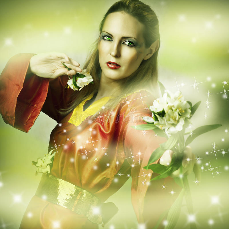 Fashion fantasy portrait of magic woman. Fairytale forest elf with flower making magic stock image