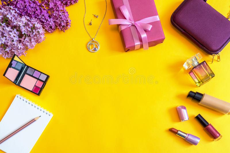 Fashion female accessories, flowers, cosmetics, perfume and jewelry on bright yellow background. Feminine concept, greeting card. For women`s or mother`s day stock photo