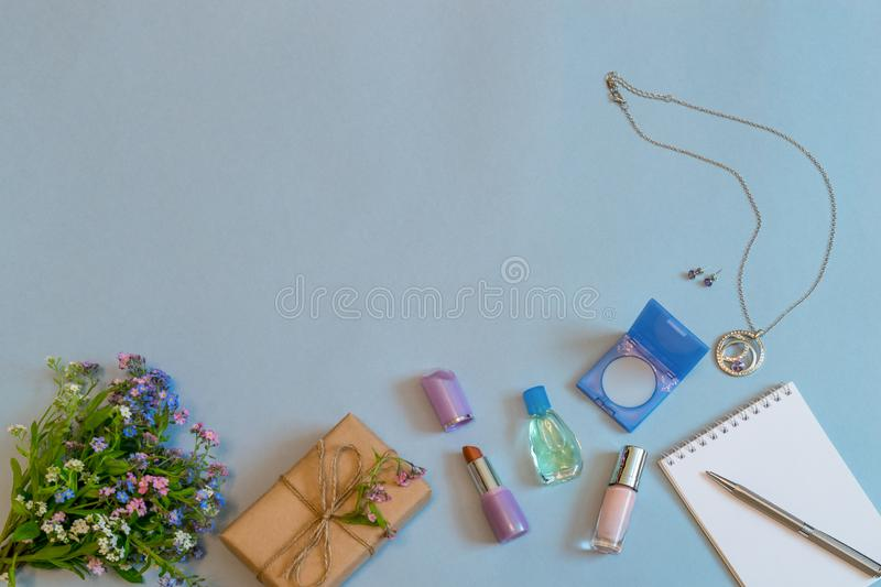 Fashion female accessories, flowers, cosmetics, perfume and jewelry on light blue pastel background. Feminine concept, greeting royalty free stock image