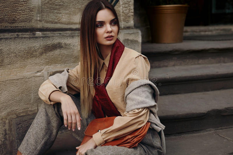 Fashion Female Model In Fashionable Clothes Posing In Street. Portrait Of Beautiful Woman In Stylish Fall Or Spring Clothing : Shirt, Scarf, Pants, Bag Sitting stock images