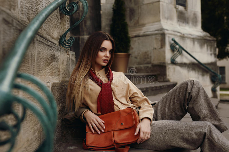 Fashion Female Model In Fashionable Clothes Posing In Street. Portrait Of Beautiful Woman In Stylish Fall Or Spring Clothing : Shirt, Scarf, Pants, Bag Sitting royalty free stock photos