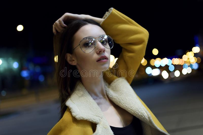 Female model posing in yellow jacket and big glasses, lit by city centre lights. Stylish womenswear stock image