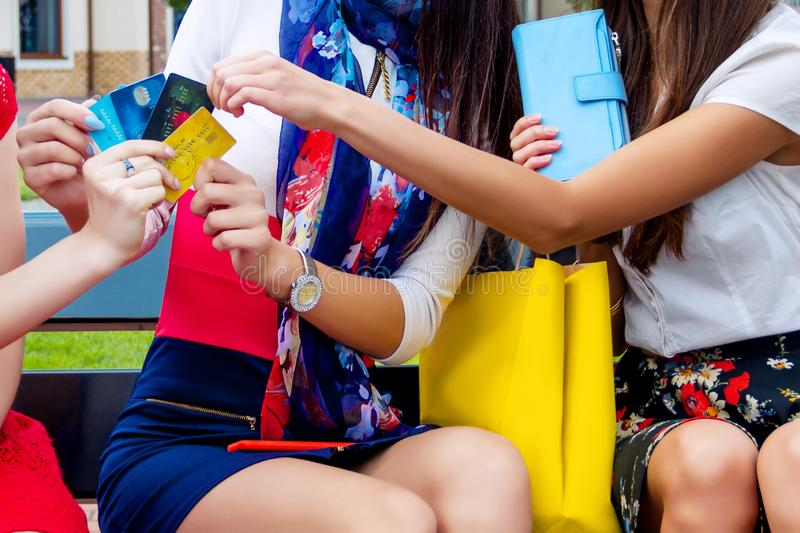 Fashion female women friends in shopping mall. Happy colorful women females adults girls friends in colorful dresses sitting outdoor before shopping in shopping royalty free stock photos