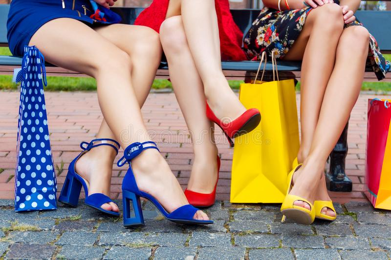 Fashion female women friends in shopping mall. Happy colorful women females adults girls friends legs in colorful dresses sitting outdoor after shopping in royalty free stock photo