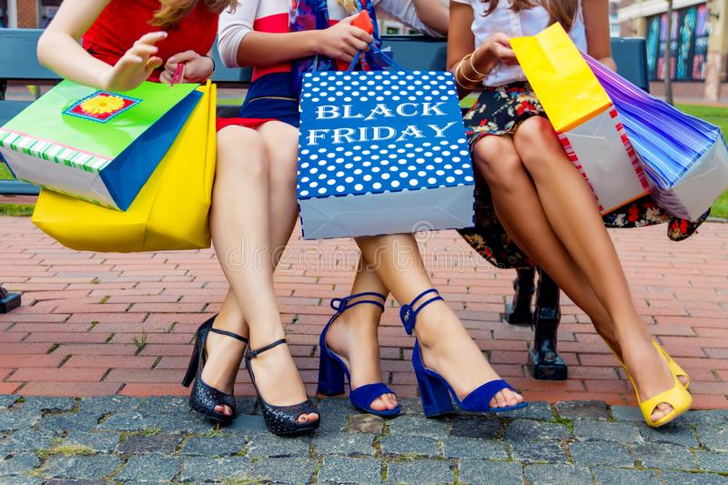 Fashion female women friends in shopping mall. Happy colorful women females adults girls friends legs in colorful dresses sitting outdoor after shopping in stock images