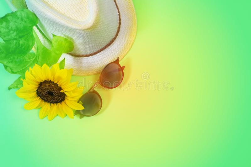 Fashion flatlay with sunglasses, straw boater hat and bright big yellow sunflower royalty free stock photography
