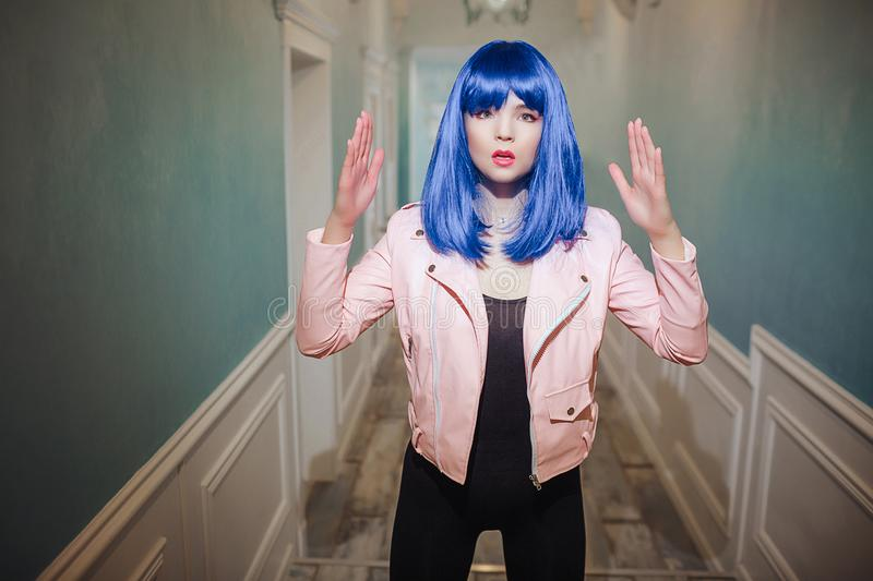 Fashion freak. Glamour synthetic girl, fake doll with blue hair is looking at the camera while standing in long corridor stock images