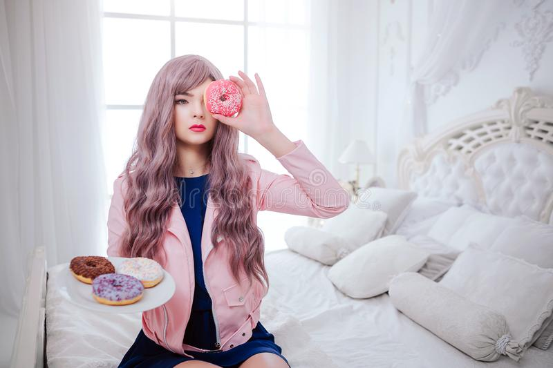 Fashion freak. Glamour synthetic girl, fake doll with empty look and long lilac hair is holding pink donut in front of. Face while sitting in white bedroom royalty free stock photo