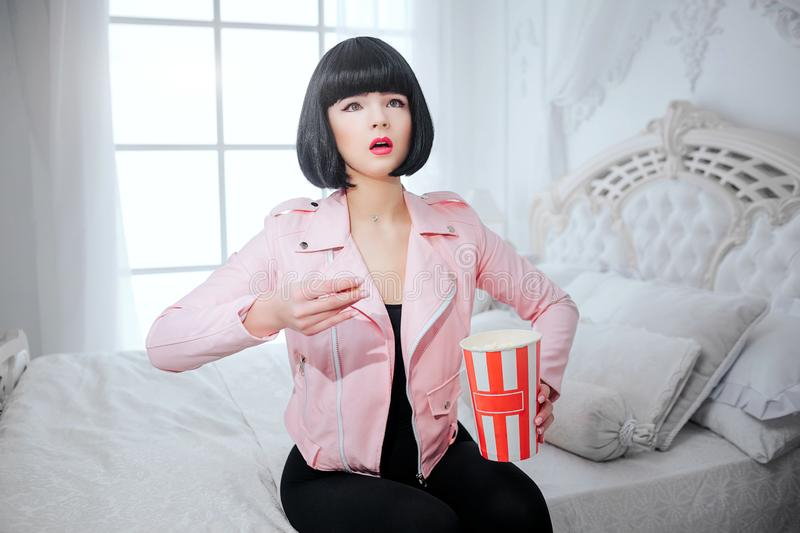 Fashion freak. Glamour synthetic interested girl, fake doll with short black hair is holding popcorn and looking TV royalty free stock photography