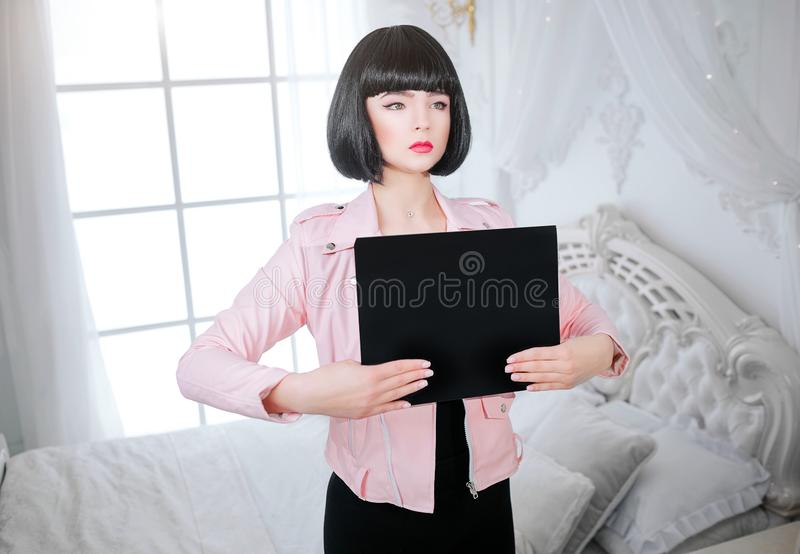 Fashion freak. Your text here. Glamour synthetic girl, fake doll with short black hair is looking away and holding empty stock photos