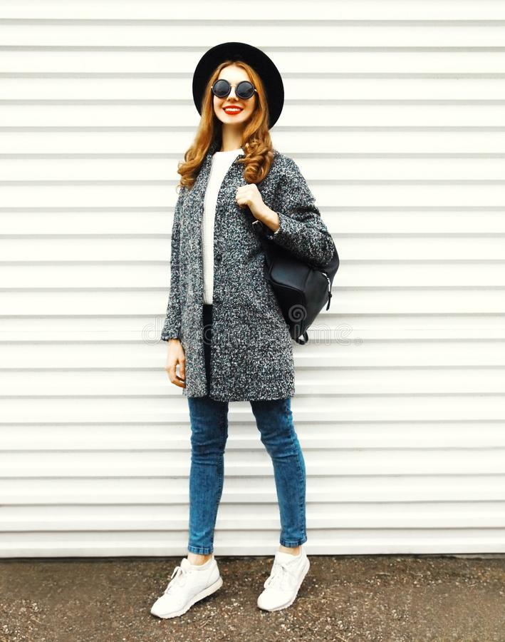 Fashion full-length woman in gray coat, black round hat posing stock image