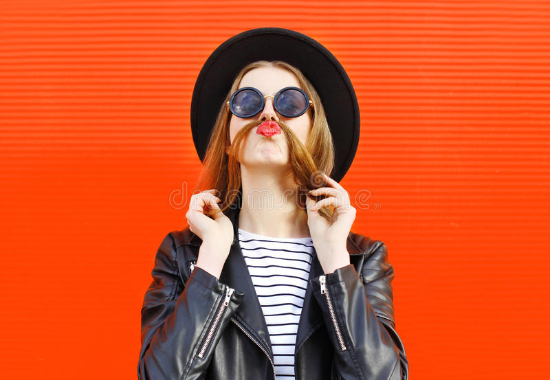 Fashion funny woman having fun shows moustache hair over colorful red royalty free stock images