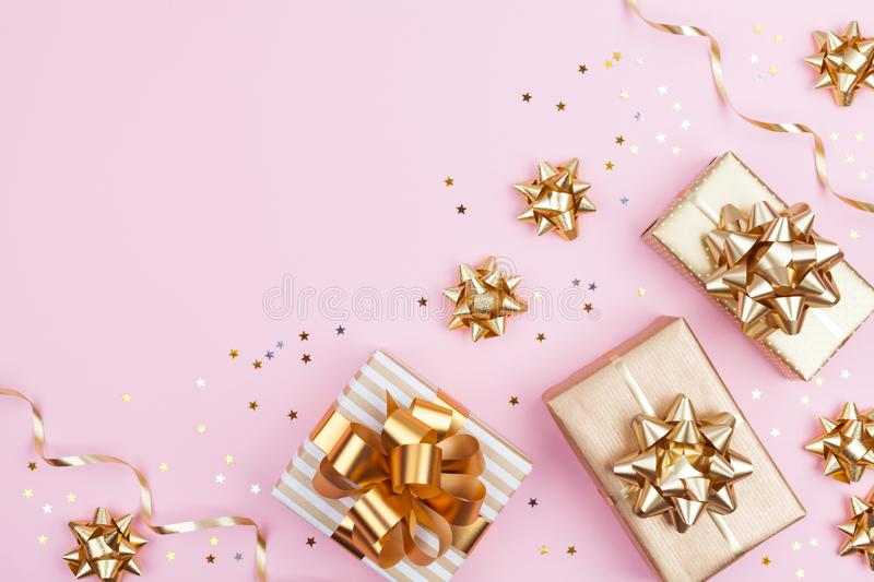Fashion gifts or presents boxes with golden bows and star confetti on pink pastel background top view. Flat lay for Christmas royalty free stock photography