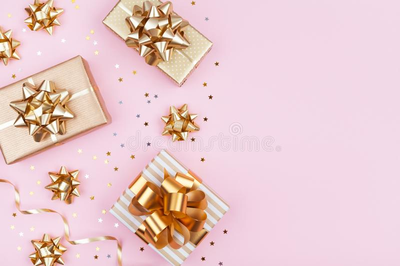 Fashion gifts or presents boxes with golden bows and star confetti on pink table top view. Flat lay for birthday or Christmas. royalty free stock image