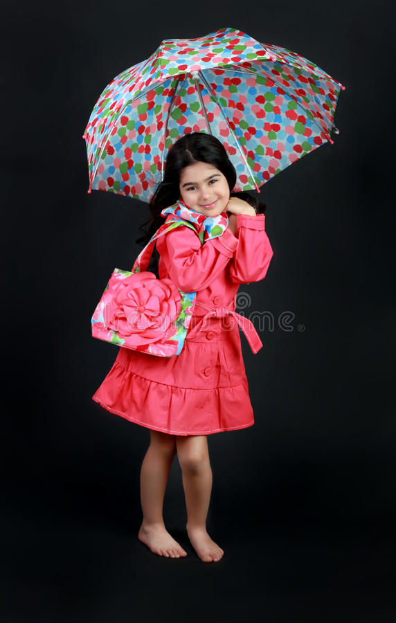 Fashion girl. Little girl wearing a rain coat, scarf with matching purse and and holding an umbrella stock photo