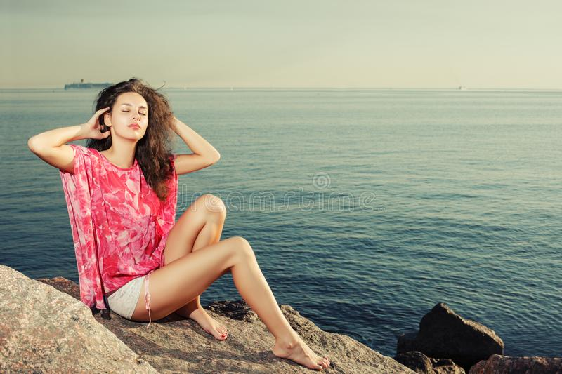 Fashion girl on the beach on rocks against the background of the. Water. Tanned slim beautiful woman model with long legs near the sea. Summertime scene about royalty free stock image