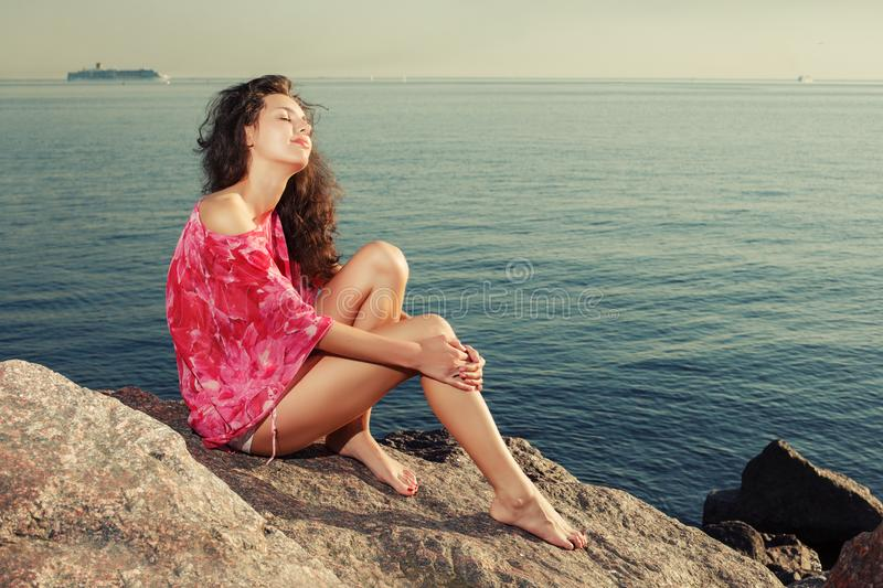 Fashion girl on the beach on rocks against the background of the. Water. Tanned slim beautiful woman model with long legs near the sea. Summertime scene about royalty free stock images