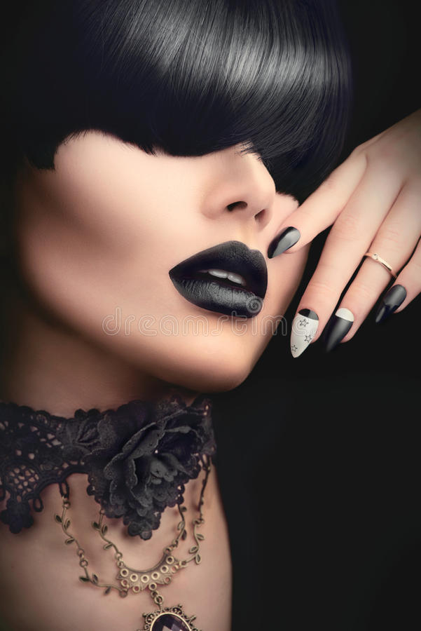 Fashion girl with black gothic hairstyle, makeup, manicure and accessories stock photography