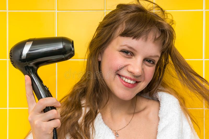 Fashion girl with black hair dryer dries her hair stock image
