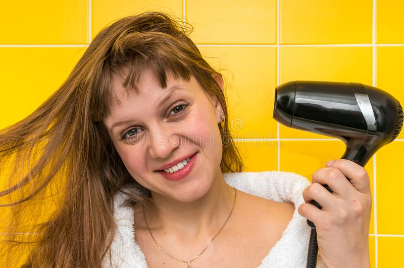 Fashion girl with black hair dryer dries her hair royalty free stock photo