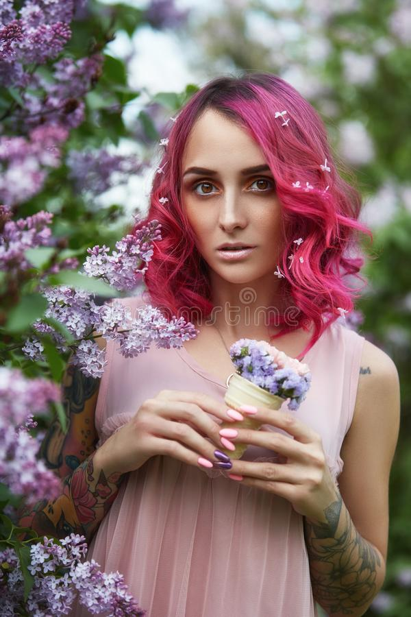Fashion girl with bright red dyed hair in Apple and lilac flowers. Creative color bright pink, colorist. Woman walks in a Park. Enjoys the spring. Beautiful stock photos