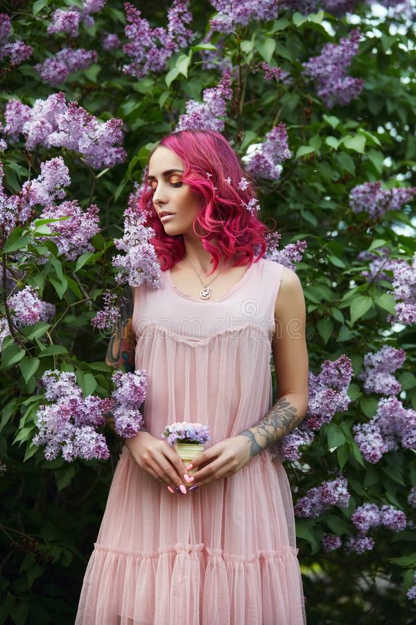 Fashion girl with bright red dyed hair in Apple and lilac flowers. Creative color bright pink, colorist. Woman walks in a Park. Enjoys the spring. Beautiful royalty free stock images