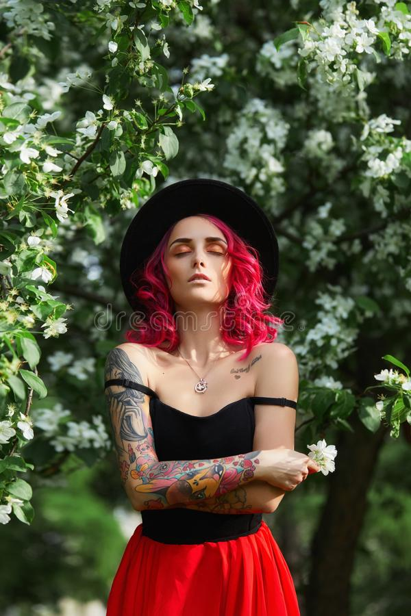 Fashion girl with bright red dyed hair in Apple and lilac flowers. Creative color bright pink, colorist. Woman walks in a Park. Enjoys the spring. Beautiful stock photography
