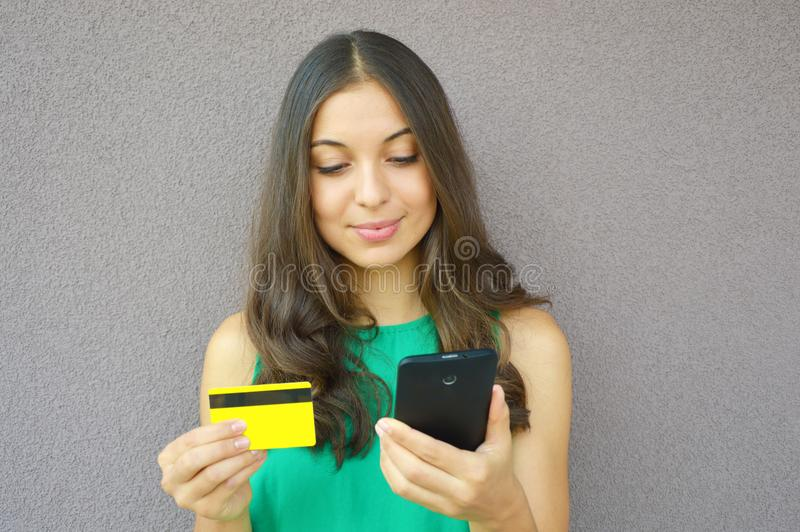 Fashion girl buying online with smart phone and credit card isolated on violet background royalty free stock photos