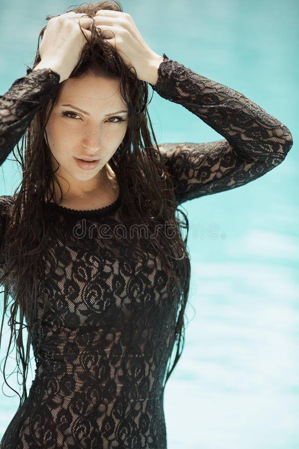 Fashion girl clothes in water. Portrait of the woman relaxing in black fashion dress in pool. Creative photosessin of beautiful caucasian girl royalty free stock photos