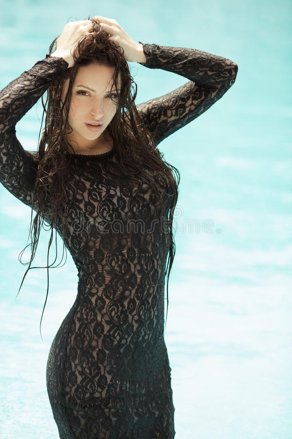 Fashion girl clothes in water. Portrait of the woman relaxing in black fashion dress in pool. Creative photosessin of beautiful caucasian girl stock photography