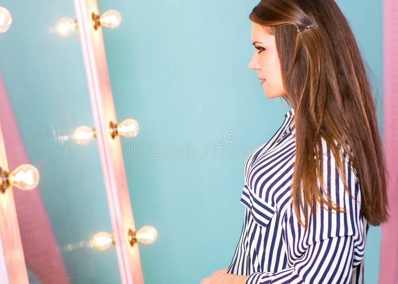Fashion girl dresses in front of a mirror in a striped shirt on stock photos