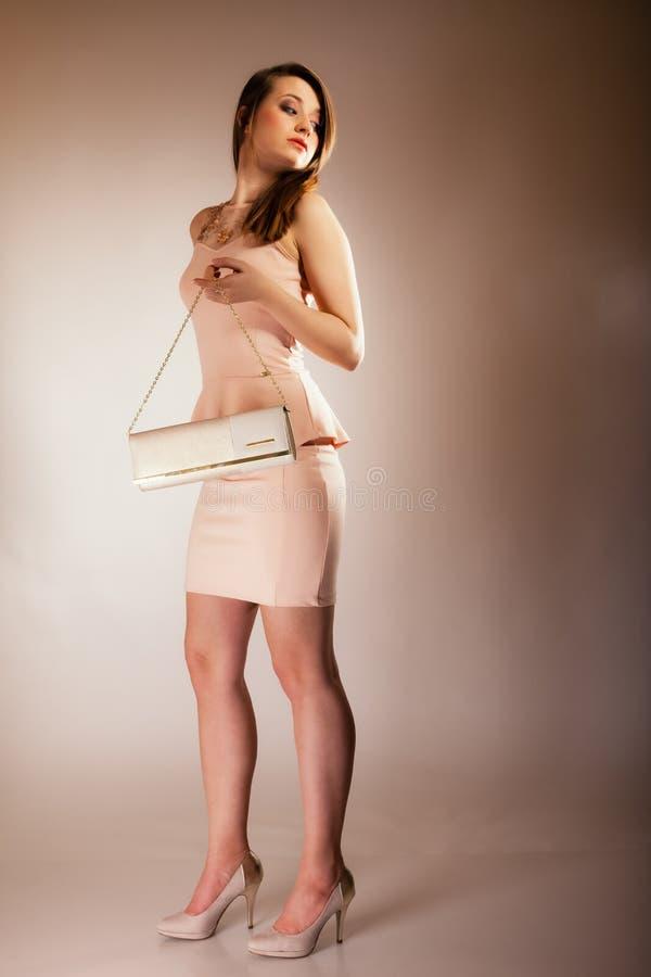 Fashion girl with elegant handbag bag. Female elegance. Full length of attractive girl young woman with elegant handbag bag luxury accessory on gray stock photo