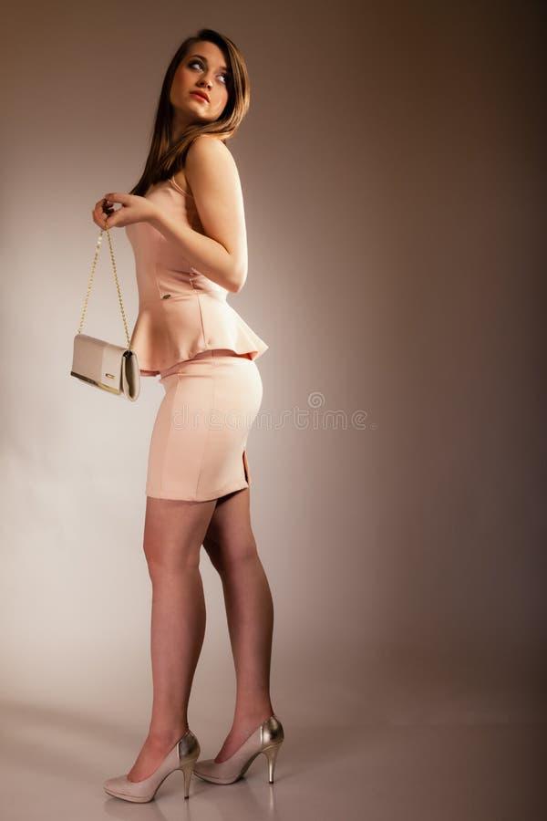 Fashion girl with elegant handbag bag. Female elegance. Full length of attractive girl young woman with elegant handbag bag luxury accessory on gray stock photos