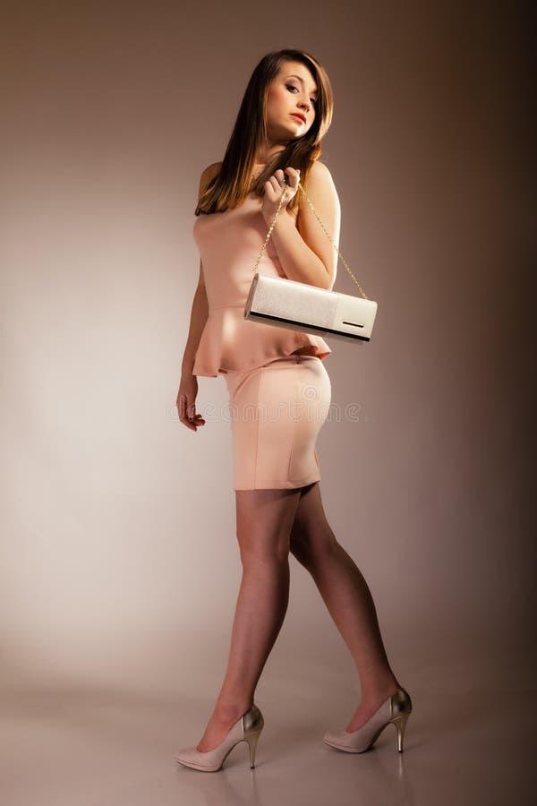 Fashion girl with elegant handbag bag. Female elegance. Full length of attractive girl young woman with elegant handbag bag luxury accessory on gray stock photography