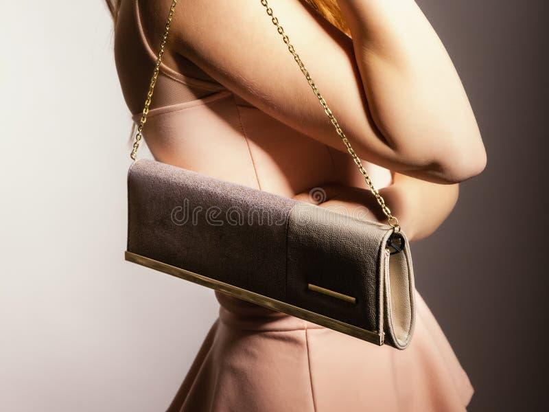 Fashion girl with elegant handbag bag. Female elegance. girl young woman holding in hand elegant handbag bag luxury accessory on gray royalty free stock image