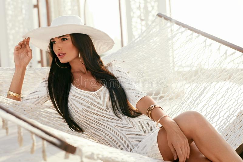 Fashion Girl In Elegant White Hat And Fashionable Clothes. Portrait Of Beautiful Woman With Long Hair Wearing Stylish Sun Hat And Dress Relaxing On Hammock In stock image