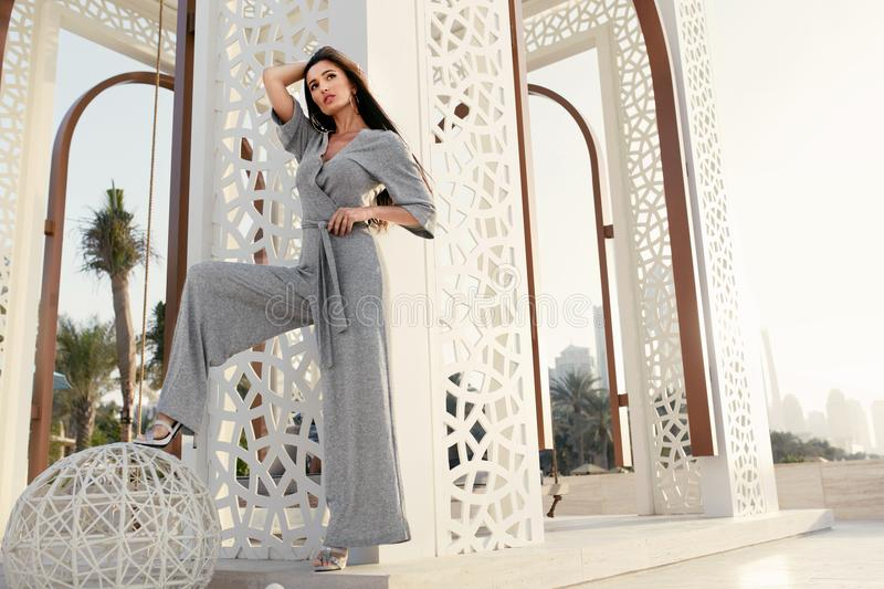 Fashion Girl. Fashionable Model In Fashion Clothes Posing. Outdoors. Beautiful Young Woman Wearing Stylish Trendy Grey Jumpsuit Relaxing At Luxury Resort In stock photography