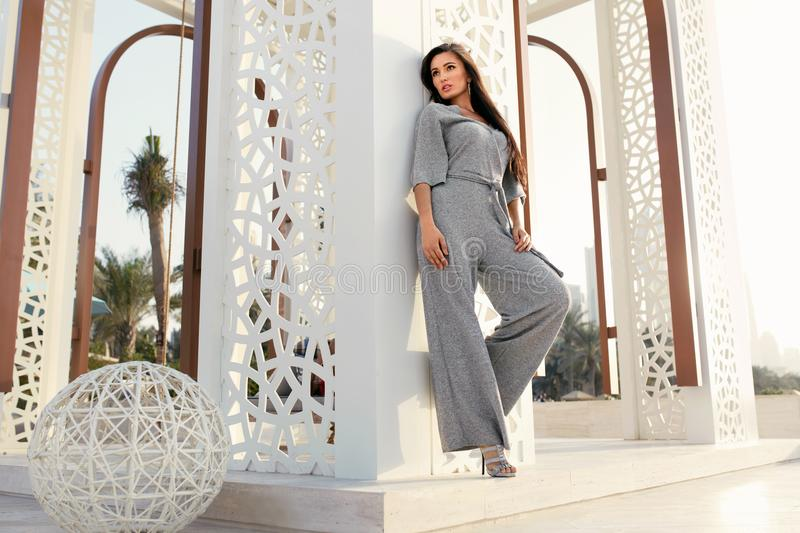 Fashion Girl. Fashionable Model In Fashion Clothes Posing. Outdoors. Beautiful Young Woman Wearing Stylish Trendy Grey Jumpsuit Relaxing At Luxury Resort In royalty free stock image