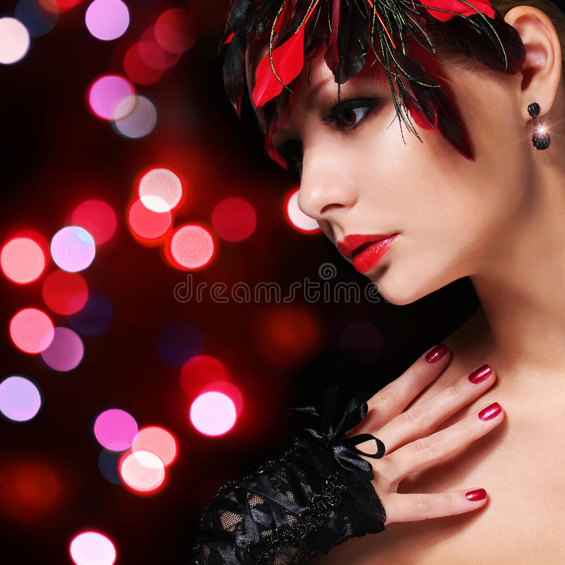 Fashion girl with feathers. Glamour young woman with red lipstick and lace gloves over Bokeh background. Portrait. Evening Makeup stock photography