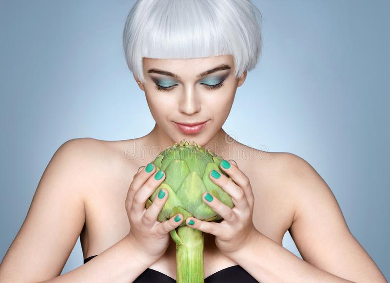 Fashion girl with fresh artichoke. Photo of blonde girl on blue background. Detox concept stock images